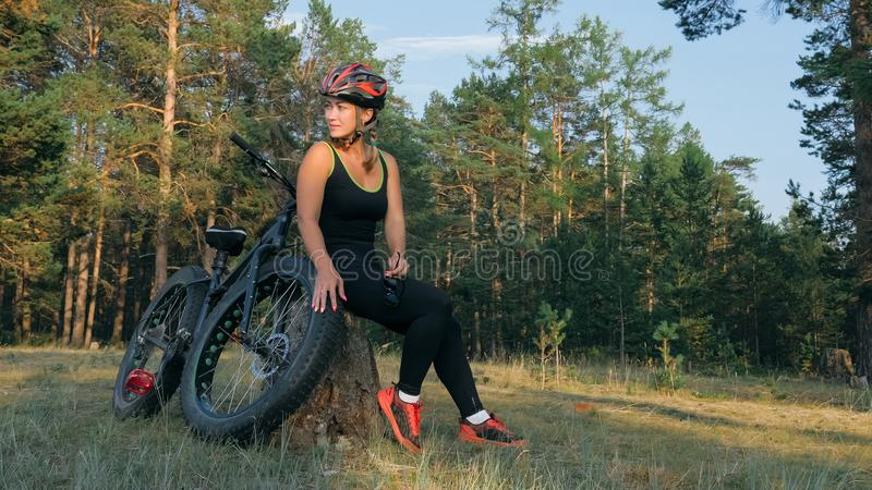 Fat bike also called fatbike or fat-tire bike in summer riding in the forest. Beautiful girl and her bicycle in the forest. She poses and smiles to the royalty free stock photography