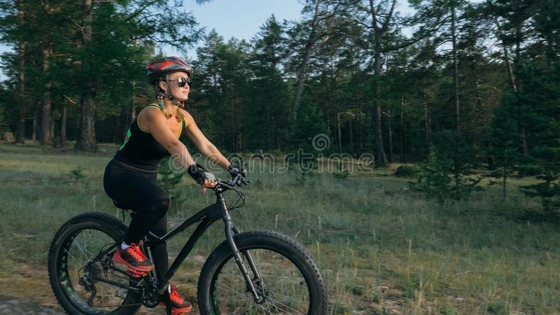 Fat bike also called fatbike or fat-tire bike in summer riding in the forest. Beautiful girl and her bicycle in the forest. She rolls her bike and poses to the stock photo