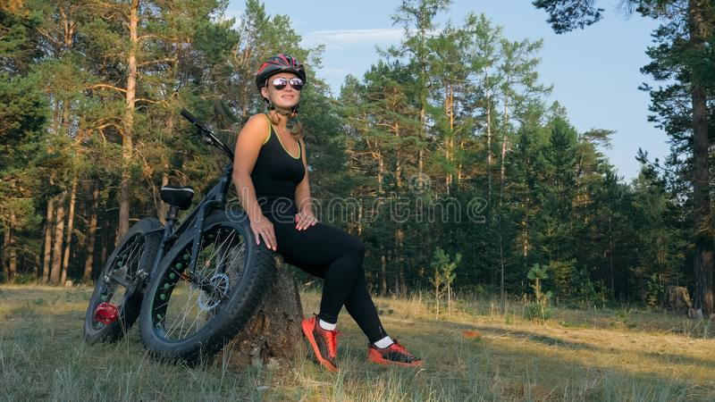 Fat bike also called fatbike or fat-tire bike in summer riding in the forest. Beautiful girl and her bicycle in the forest. She poses and smiles to the royalty free stock photos