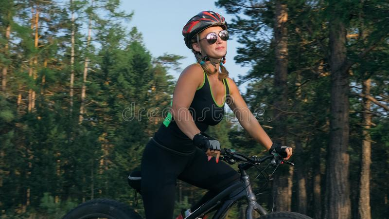 Fat bike also called fatbike or fat-tire bike in summer riding in the forest. Beautiful girl and her bicycle in the forest. She poses and smiles to the stock images