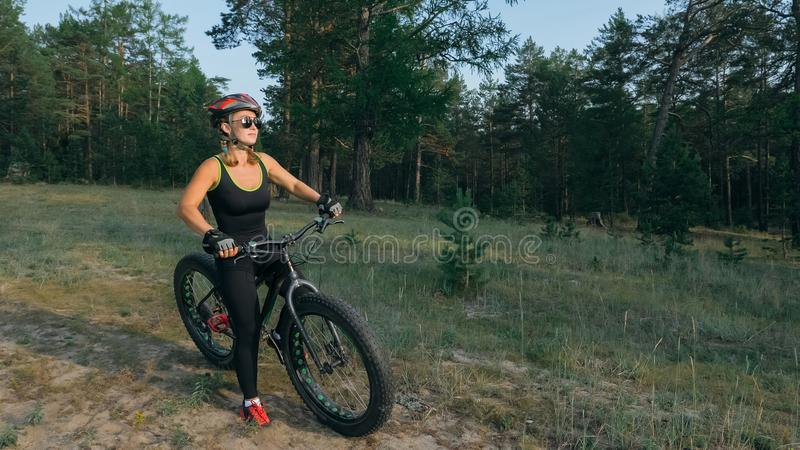 Fat bike also called fatbike or fat-tire bike in summer riding in the forest. Beautiful girl and her bicycle in the forest. She rolls her bike and poses to the royalty free stock photos