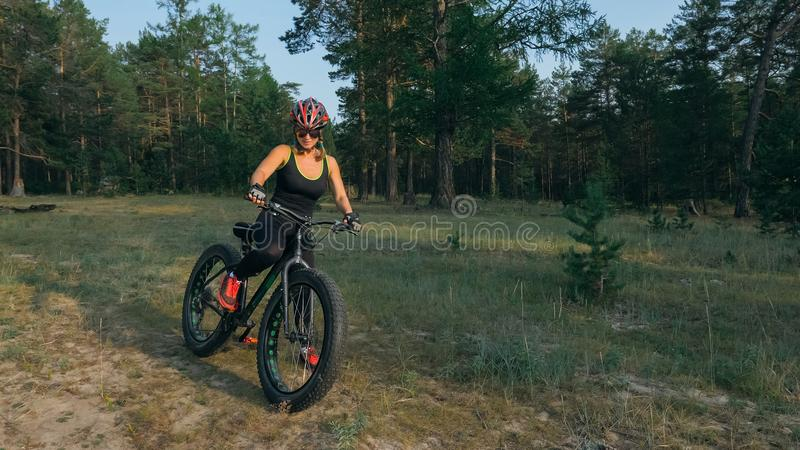 Fat bike also called fatbike or fat-tire bike in summer riding in the forest. Beautiful girl and her bicycle in the forest. She rolls her bike and poses to the royalty free stock image