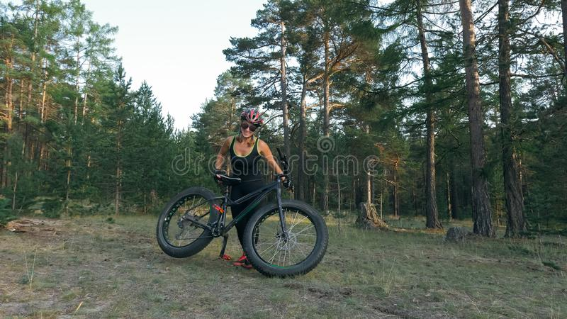 Fat bike also called fatbike or fat-tire bike in summer riding in the forest. Beautiful girl and her bicycle in the forest. She rolls her bike and poses to the royalty free stock photo
