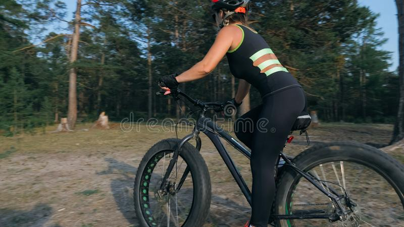 Fat bike also called fatbike or fat-tire bike in summer riding in the forest. Beautiful girl and her bicycle in the forest. She rolls her bike and poses to the stock photography