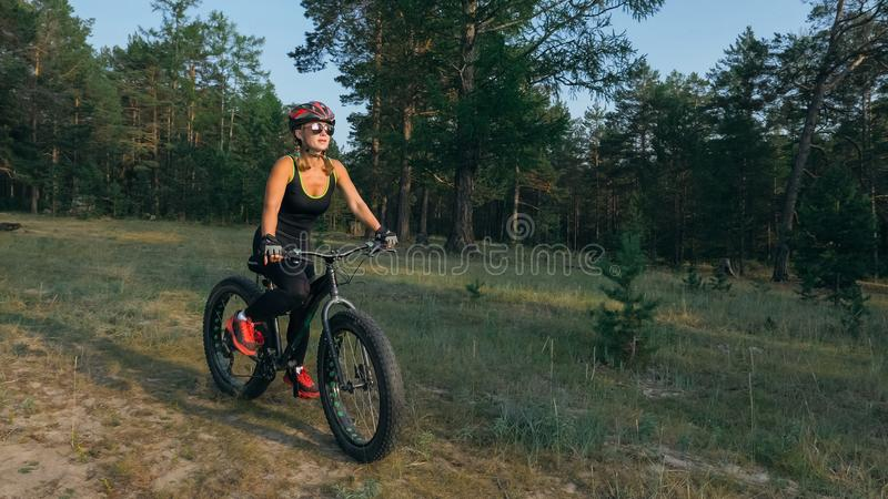 Fat bike also called fatbike or fat-tire bike in summer riding in the forest. Beautiful girl and her bicycle in the forest. She rolls her bike and poses to the stock image