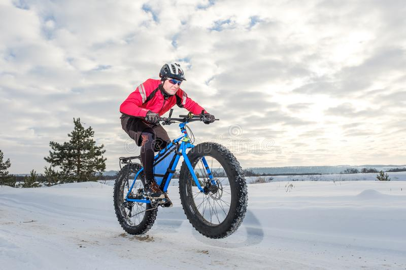 Fat bike. Fat tire bike. A young man riding fat bicycle in the winter. A young man riding fat bicycle in the winter. winter biking. Fatbike. Fat tire bike stock photos
