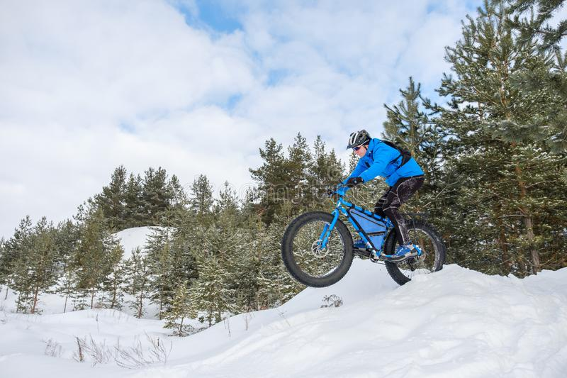 Fat bike. Fat tire bike. A young man riding fat bicycle in the winter royalty free stock photo