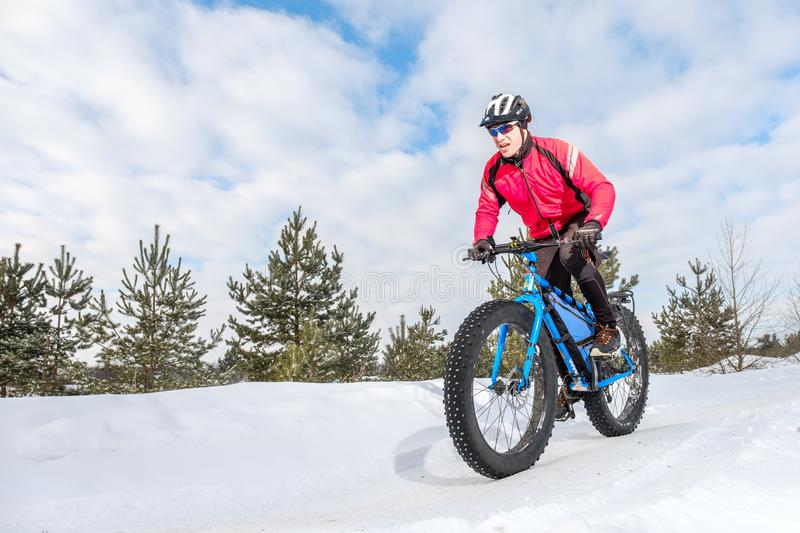 Fat bike. Fat tire bike. A young man riding fat bicycle in the winter. A young man riding fat bicycle in the winter. winter biking. Fatbike. Fat tire bike stock photography
