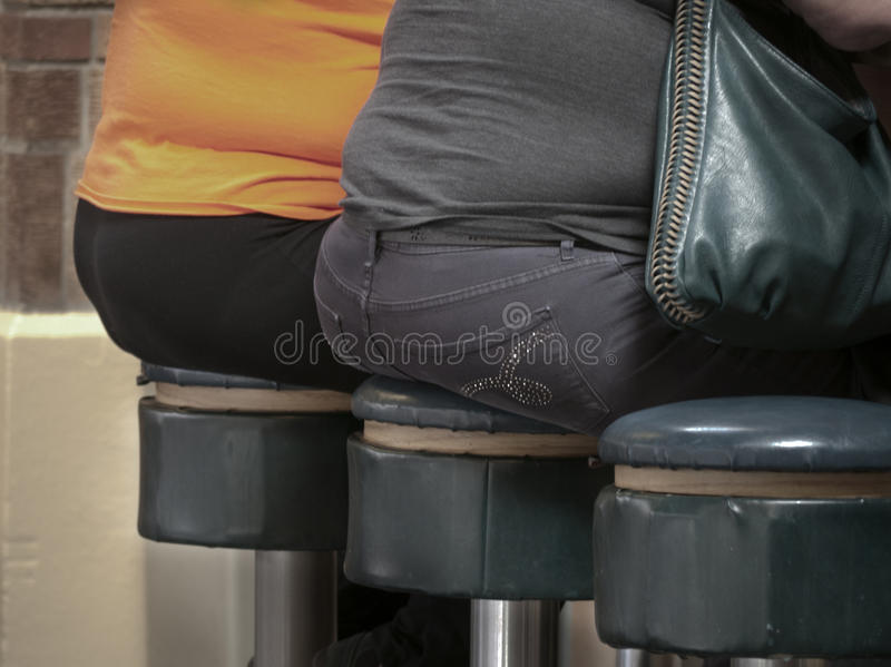 Fat bottom ladies. Sitting on round bar stools royalty free stock photos