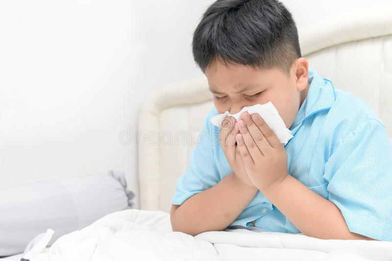 Fat boy has runny nose and blows nose into tissue. Sick child. Asian fat boy has runny nose and blows nose into tissue sitting on bed, Health care concept royalty free stock photography