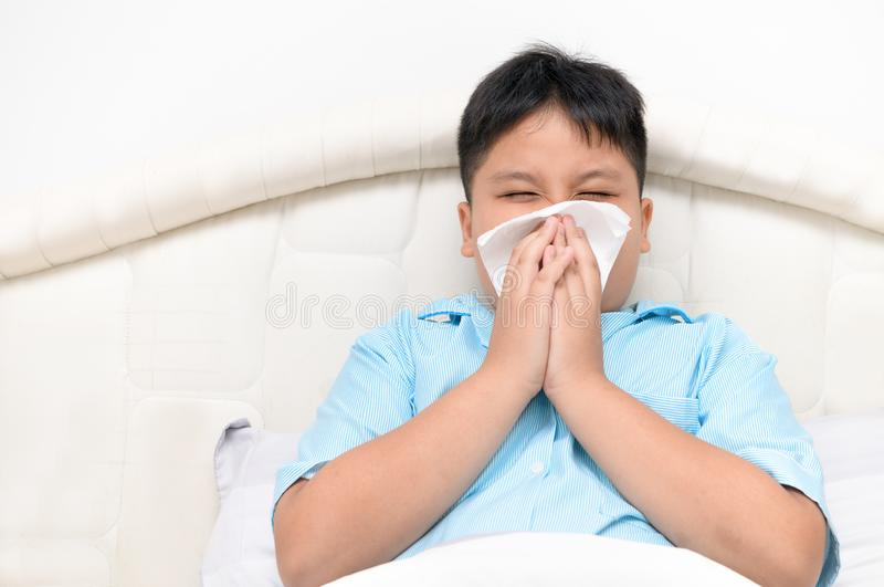 Fat boy has runny nose and blows nose into tissue. Sick child. Asian fat boy has runny nose and blows nose into tissue sitting on bed, Health care concept stock photo