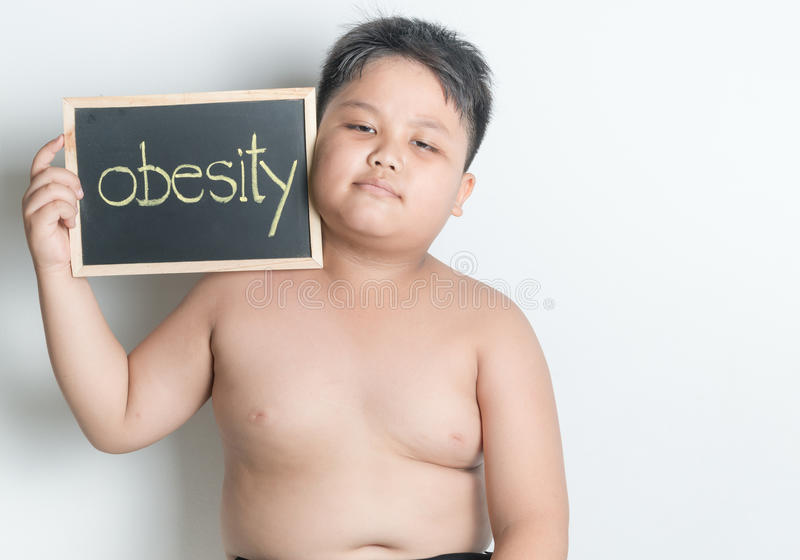 Fat boy hold blackboard. Fat boy show blackboard on gray background, concept to diet, lose him weight stock photos