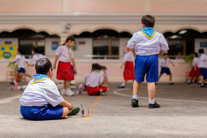 Fat boy lonely sitting in school playground watching friend playing. stock photo
