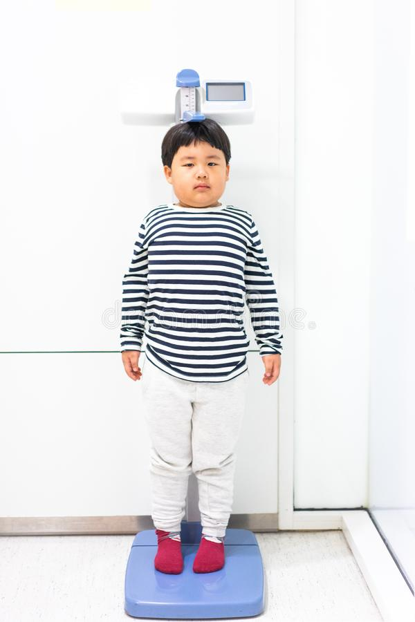 A fat boy is measuring his height himself in hospital stock photo