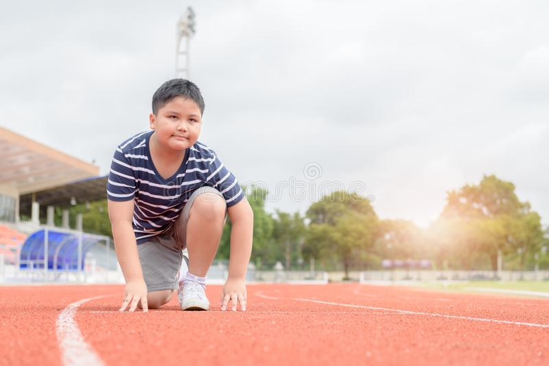 Fat boy in starting position ready for running. Fit and confident fat boy in starting position ready for running. kid athlete about to start a sprint looking at royalty free stock photos