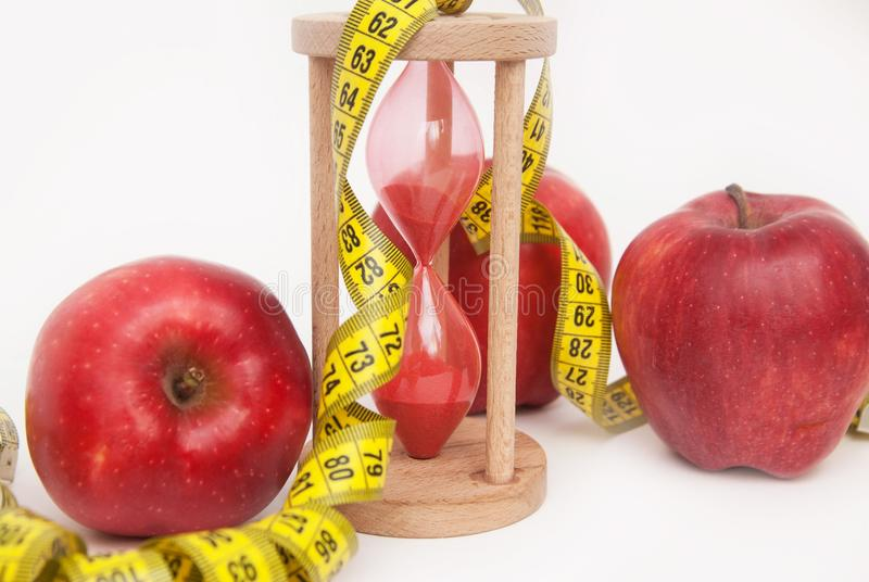 Fat Burning and Weight loss process. Diet and Fitness Concept. Red Apples and Tape Measure Isolated, close up. White Background. V stock photo