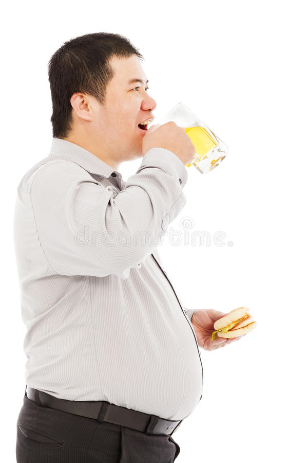 Fat business man drinking beer mug and eating hamburger. Over white background stock photography