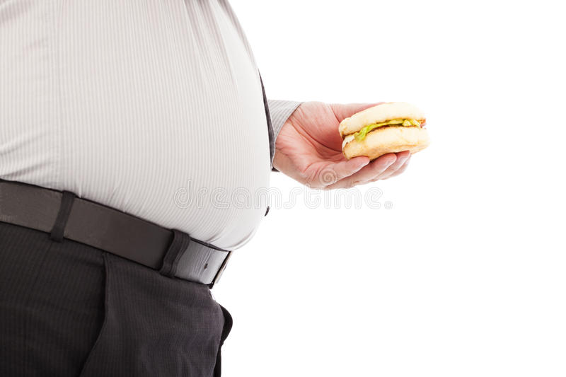 Fat business man holding a hamburger fastfood. In studio royalty free stock photos