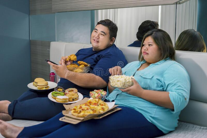 Fat couple holding junk foods while watching tv royalty free stock image