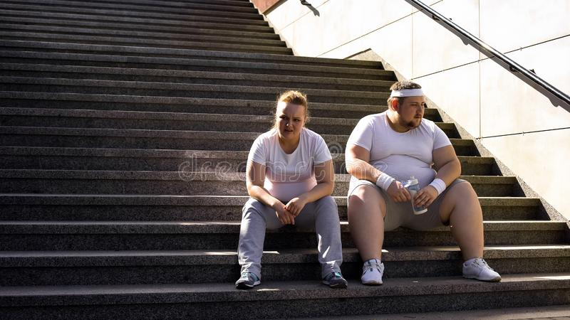 Fat couple sitting on stairs, exhausted after physical trainings, togetherness. Stock photo royalty free stock image