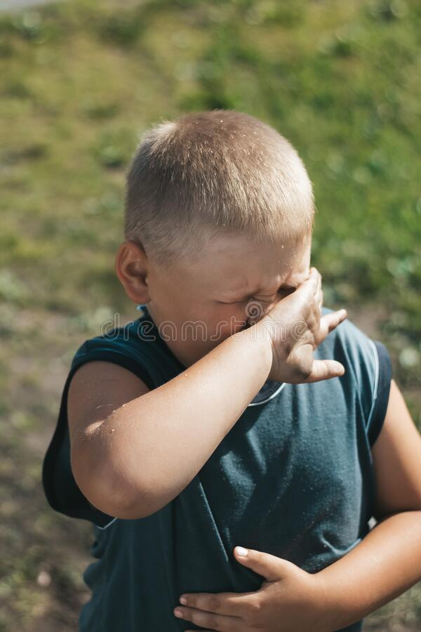 Fat dirty boy covers his face from spray. A child with blond hair and a dirty adult t-shirt. Unsanitary conditions. Street games o. F a boy. The problem of stock photos