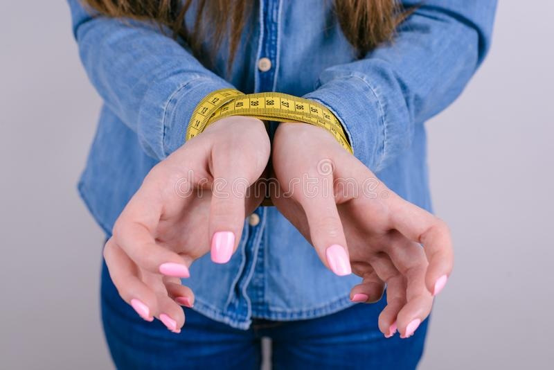 Fat food anorexia nervosa bulimia concept. Cropped closeup photo of unsatisfied tired exhausted unhappy sad upset teen teenager. Showing tied hands  grey stock photos