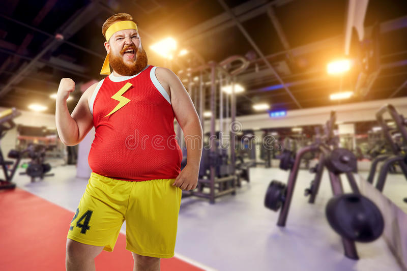 Fat funny man winner smiles in sports clothes in the gym. royalty free stock photography