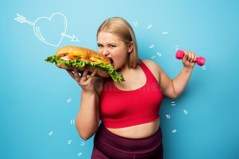 Fat girl does gym and want to eat a sandwich. Concept of indecision and doubt stock photos
