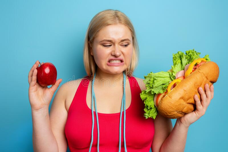 Fat girl does gym and want to eat a sandwich. Concept of indecision and doubt royalty free stock images