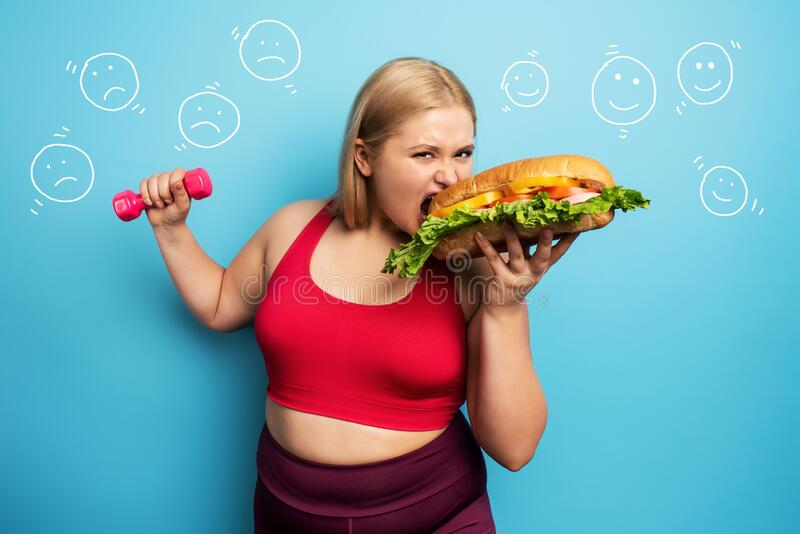 Fat girl does gym and want to eat a sandwich. Concept of indecision and doubt royalty free stock photography