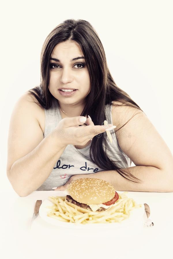 A fat girl eating fast food royalty free stock photos