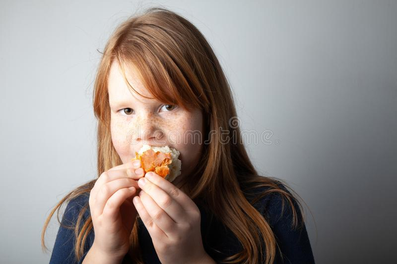 Fat girl eats sweet loaf. Excess calories and overeating stock photography