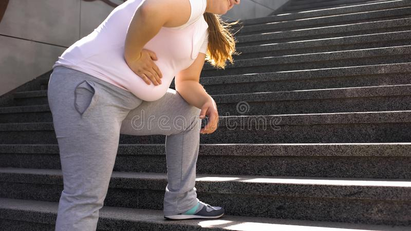 Fat girl feels ache in stomach, overweight causes health problems, back pain. Stock photo royalty free stock photography