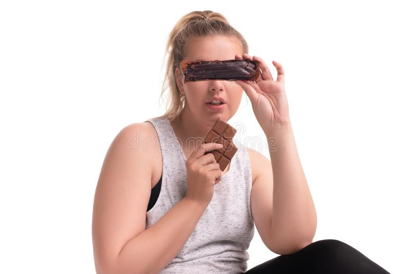 Fat girl eating chocolate and cakes isolated shot. Fat girl in sportswear eating chocolate and cakes isolated shot royalty free stock photography