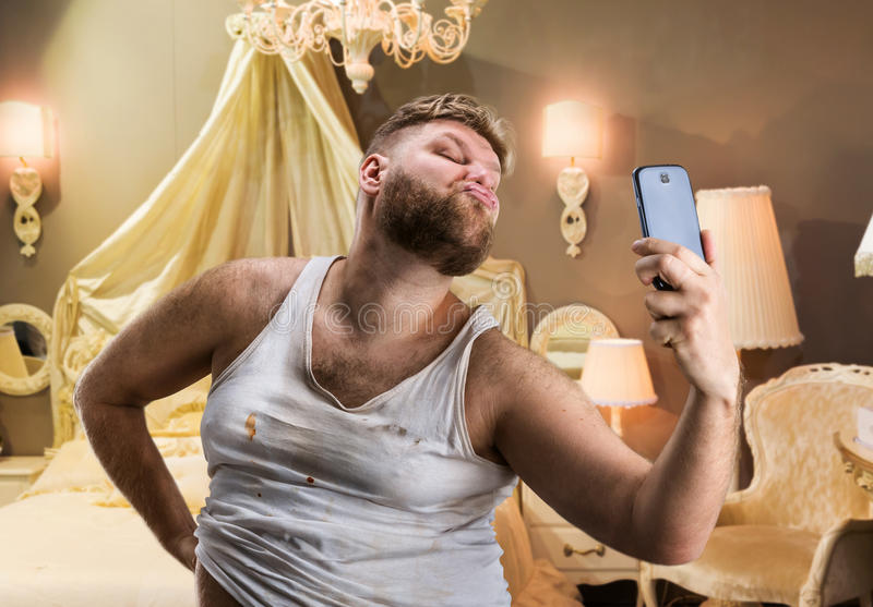 Fat glamour man takes selfie. Glamour ugly man with beard takes selfie in bedroom royalty free stock photo