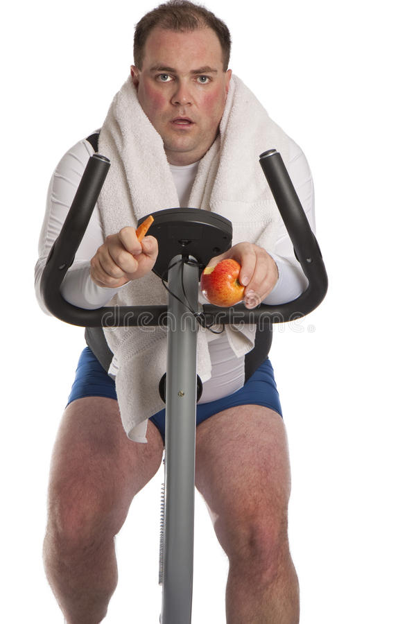 Fat guy on bike. Photo of a fat guy on a bike with a cartot and apple on a white background stock photography