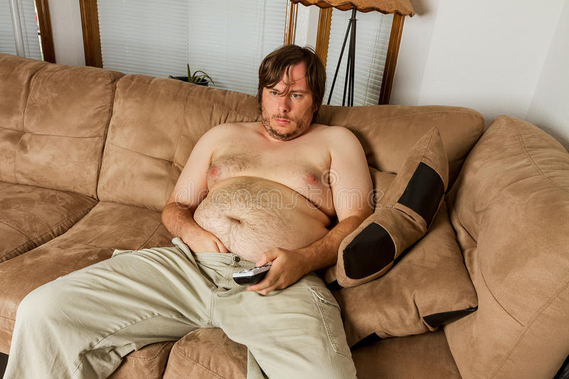 Fat guy laying on the couch stock photo