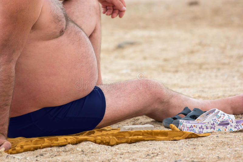 Fat guy sitting on beach. Caucasian man with big belly. Impact of passive lifestyle. Danger of diabetes development royalty free stock image