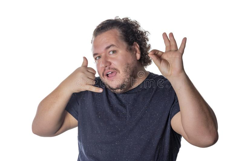 Fat handsome guy showing call me sign. Man in casual keeping hand at ear and imitating phone talk stock images