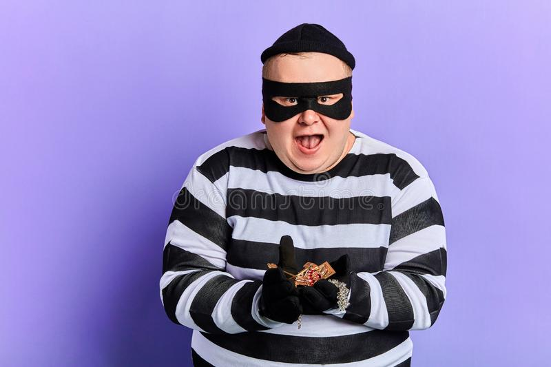 Fat happy excited burglar holding jewel in palms and looking at the camera. Fat happy excited burglar in mask and stiped clothes holding jewel in palms and royalty free stock photo
