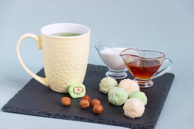 Fat keto peanut butter, cheesecake, matcha balls and keto matcha coconut bulletproof tea in yellow cup. keto protein balls and stock image