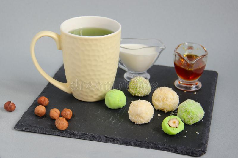 Fat keto peanut butter, cheesecake, matcha balls and keto matcha coconut bulletproof tea in yellow cup. keto protein balls and royalty free stock image