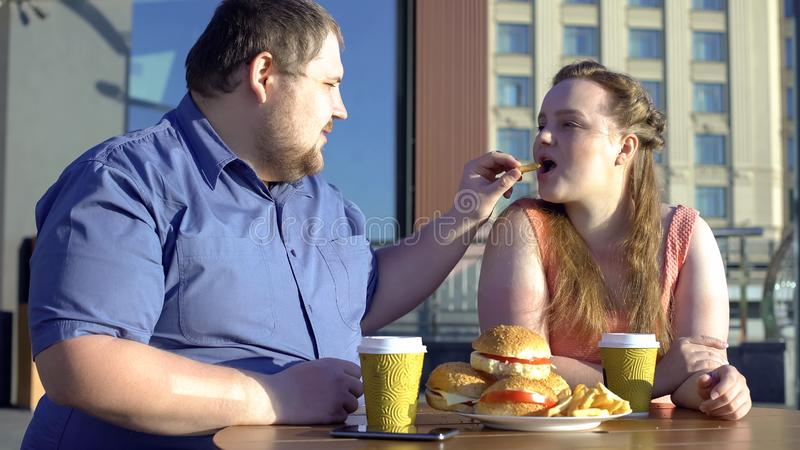Fat male treating girlfriend with fries couple eating junk food, obesity problem stock photography