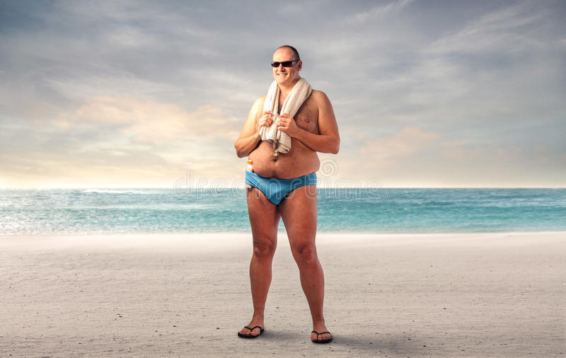Fat man at the beach stock photography