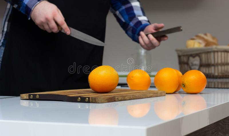 A fat man with a beard is sharpening a knife in a modern kitchen, preparing before cooking in the kitchen, freshness, vitamin royalty free stock photography