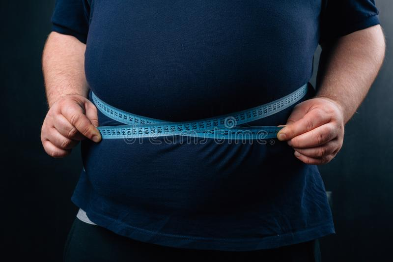 Fat man with a big belly on a dark background. Diet royalty free stock photos