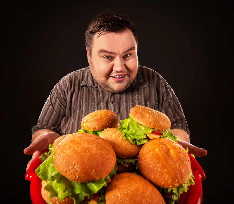 Fat man eating fast food hamberger. Breakfast for overweight person. Fat man eating fast food hamberger and carries treat for friends on tray. Breakfast for royalty free stock photos