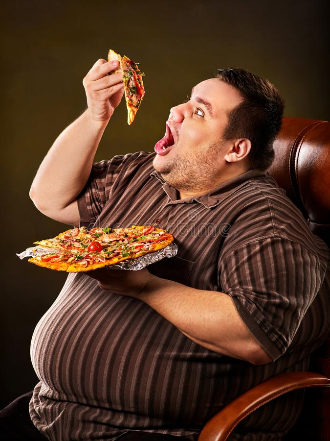 Fat man eating fast food slice pizza. Breakfast for overweight person. Diet failure of fat man eating fast food slice pizza on plate. Close up of breakfast for royalty free stock image