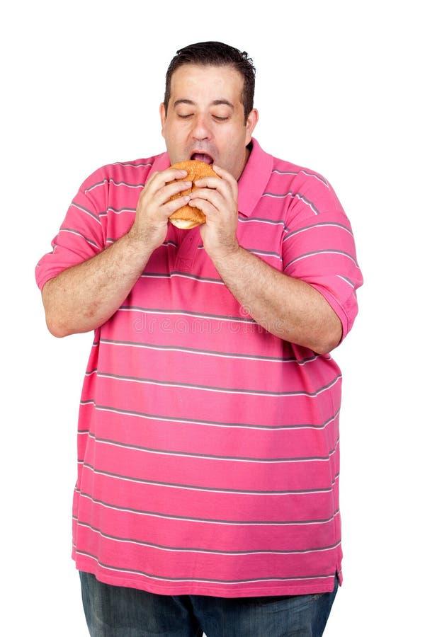 Fat man eating a hamburger royalty free stock photos