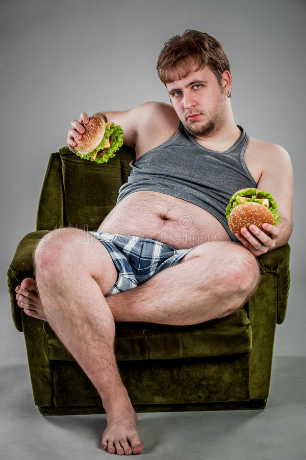 Fat man eating hamburger. Seated on armchair royalty free stock photo